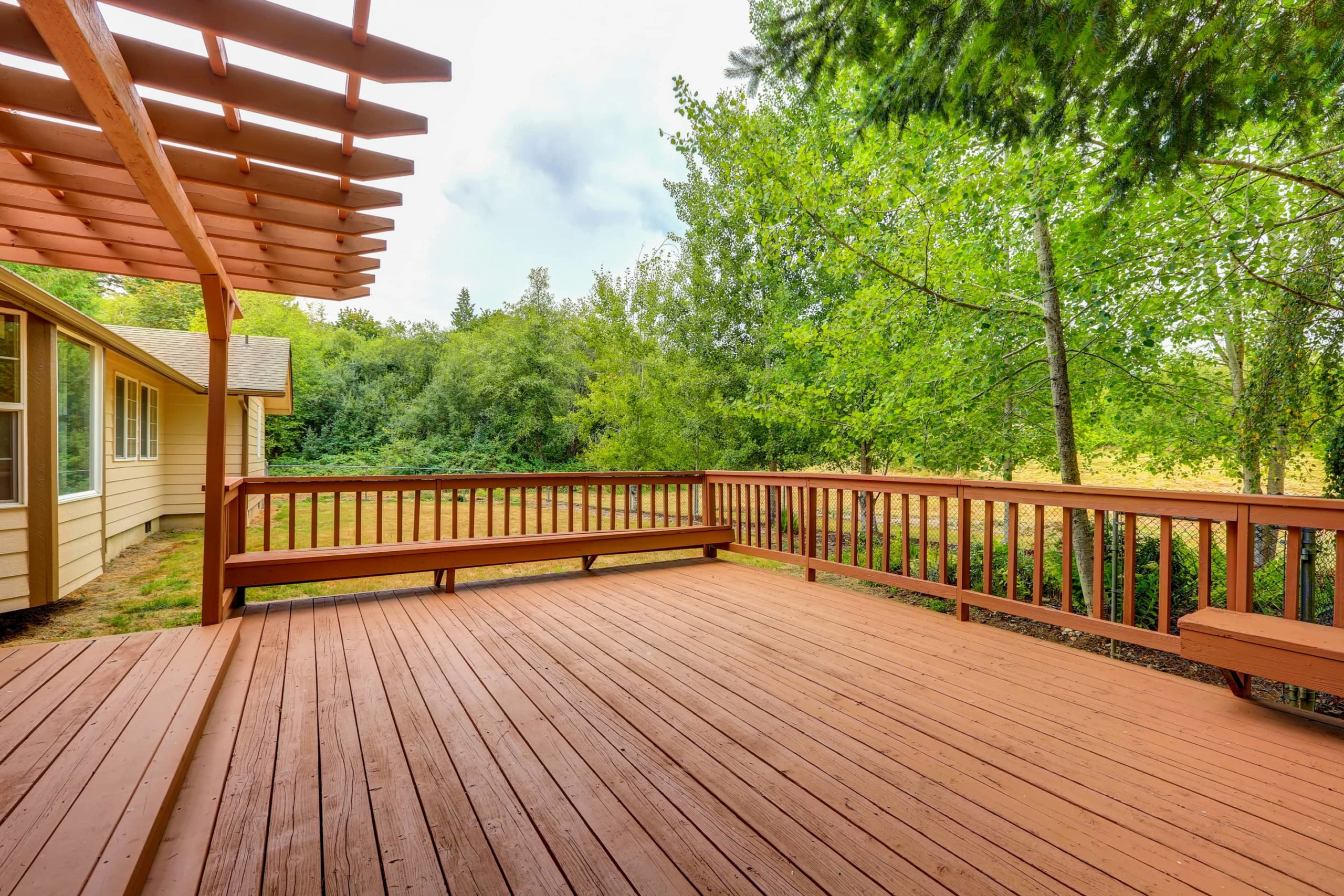 This image shows a beautifully crafted large wooden deck and pergola.