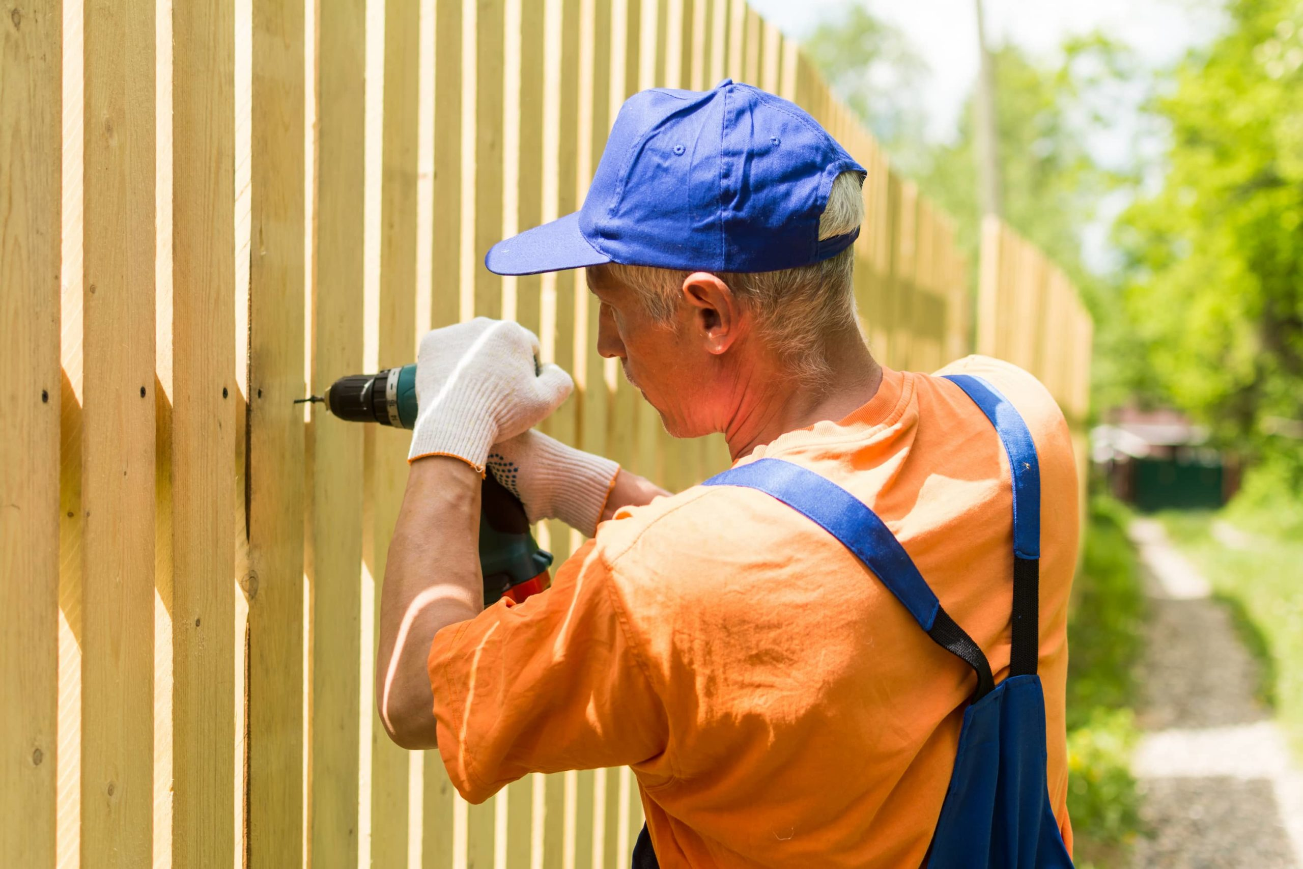 A picture of a man installing fence boards with a power drill.