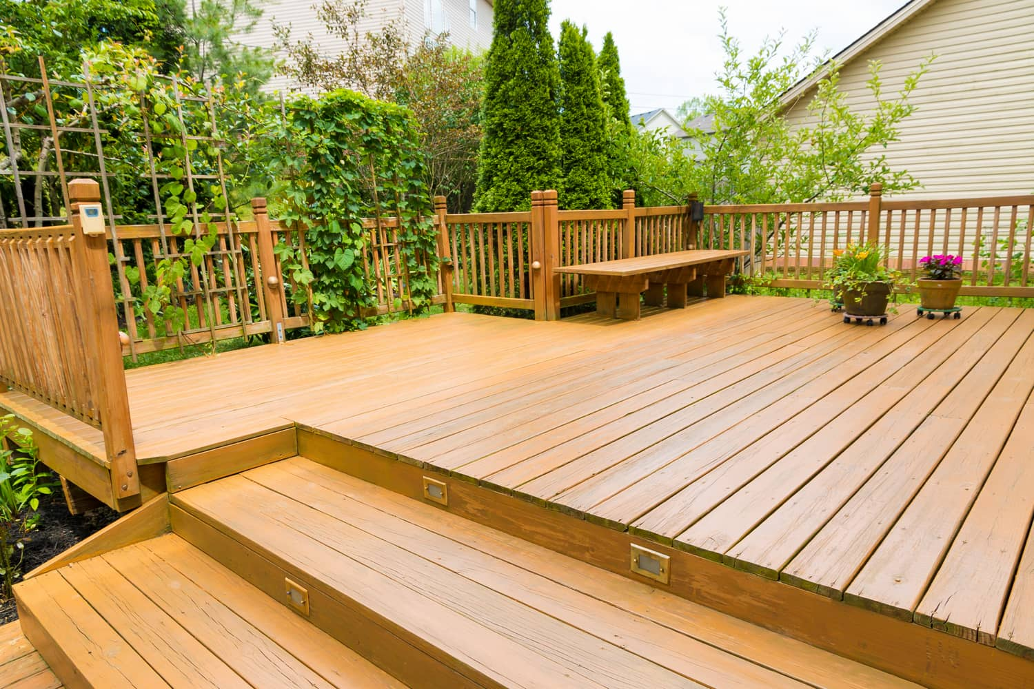 This picture is of a large wooden deck with a bench next to a garden.