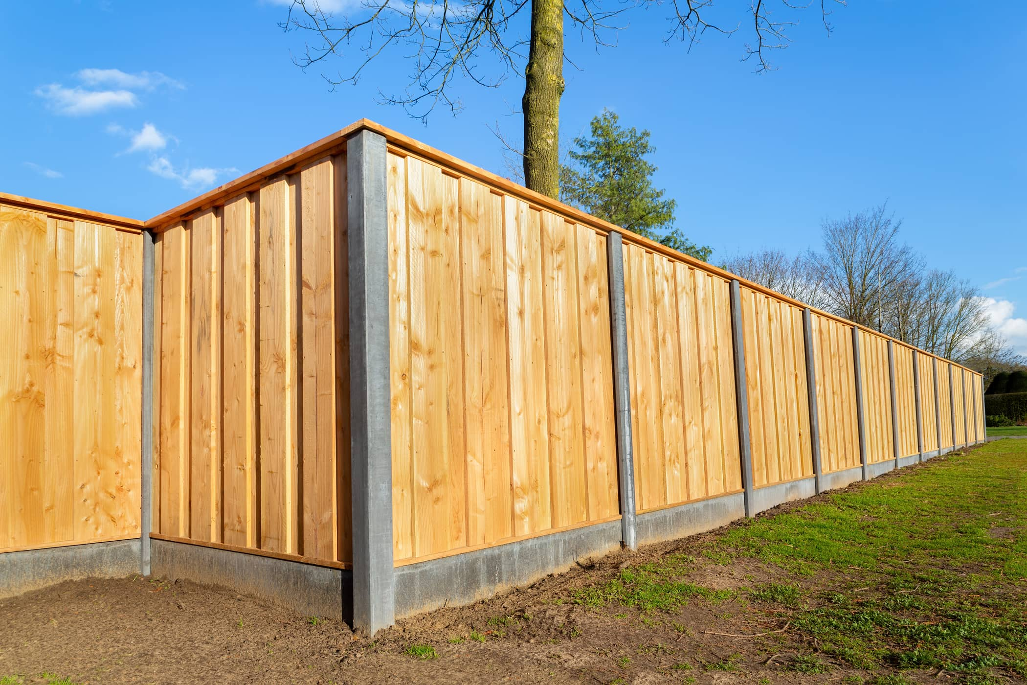 This image shows a fence that is made of both wood and concrete for extra support.