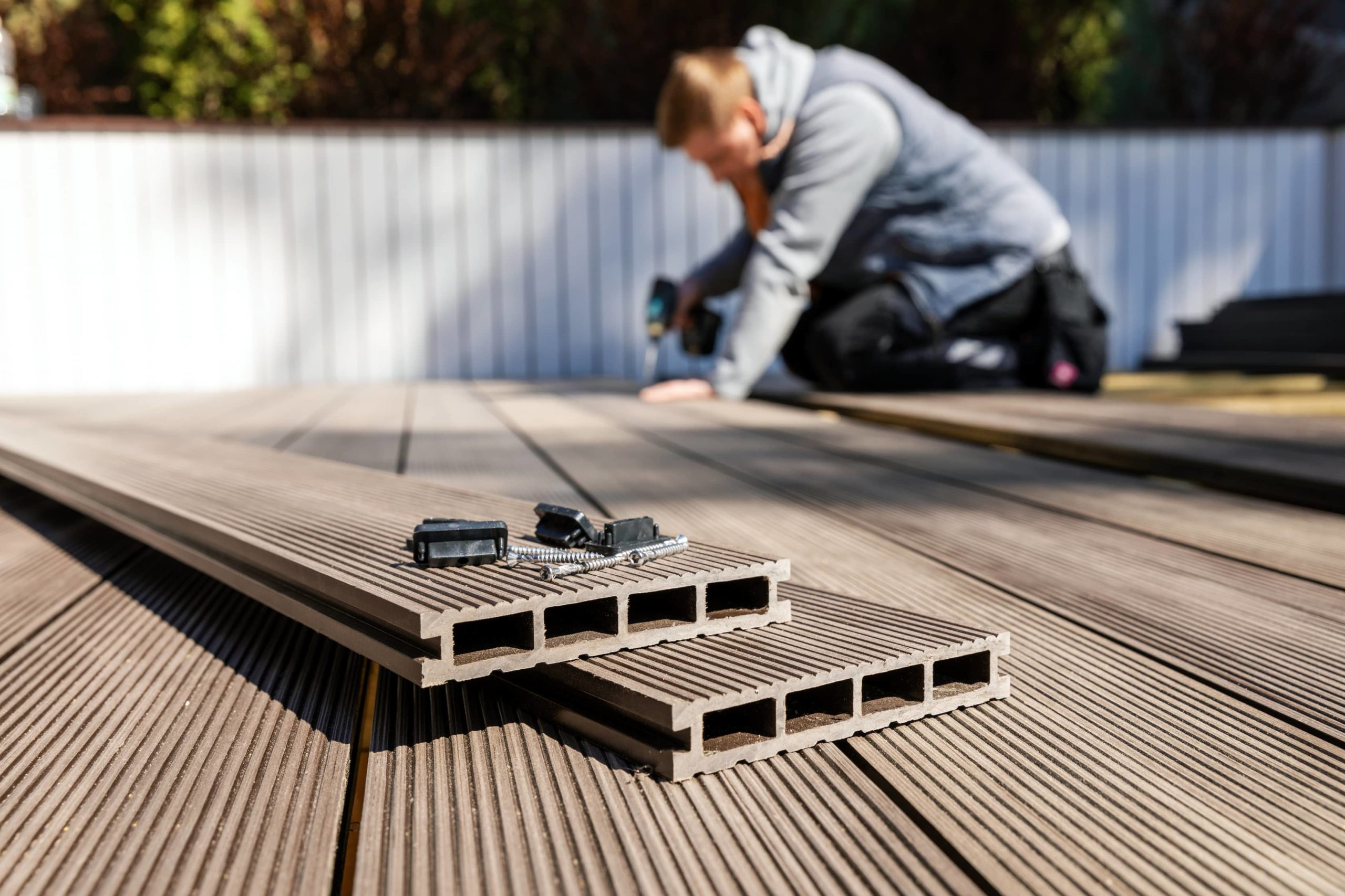This image shows an expert deck contractor installing a composite board deck.