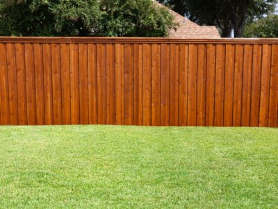 This is a brown wooden fence for a residential property next to a well manicured green lawn.